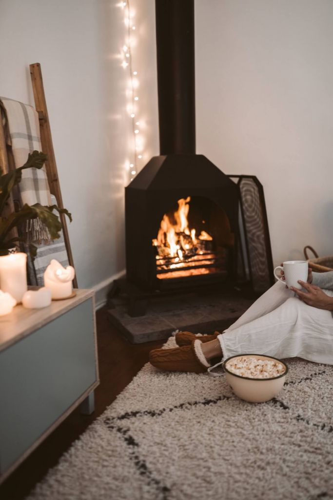 woman with popcorn relaxing next to her fireplace