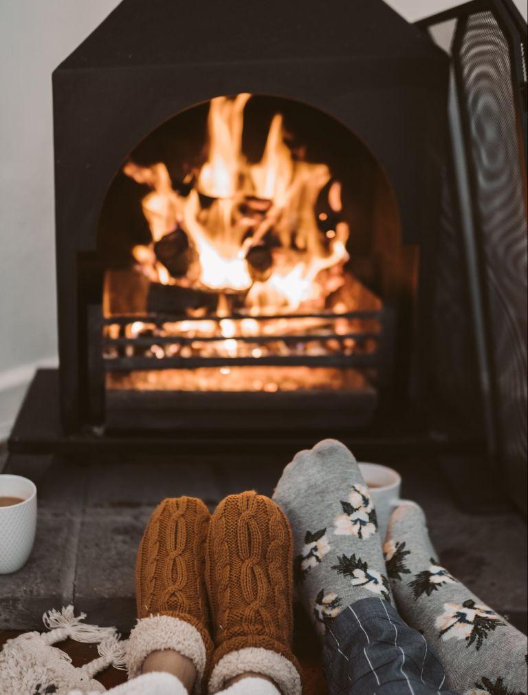 feet in socks being warmed by a fireplace