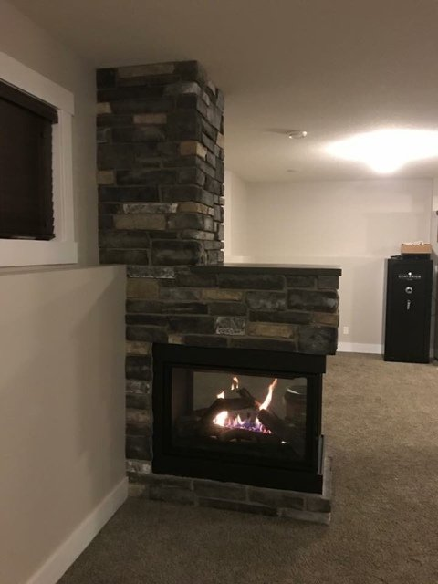 3 way wood fireplace with chimney installed into a living room space
