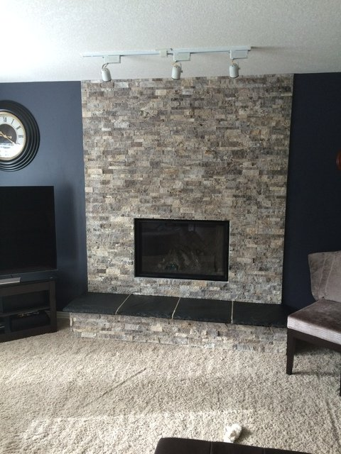 Installed Marquis Collection fireplace in a stone living room wall